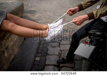 Man Pulls The Laces On The Sneakers Of His Girlfriend Sitting On The Motorcycle
