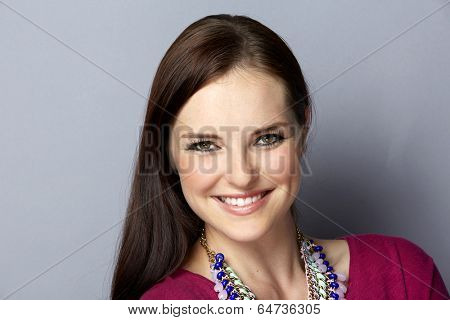 Portrait of a smiling young woman, with long brunette hair, on gray studio background, wearing pink purple top and bright statement necklace