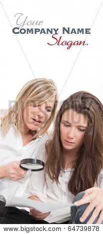 A pair of beautiful young women examining a document thou a magnifying glass