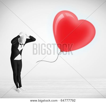Cute guy in morpsuit body suit looking at a red balloon shaped heart poster