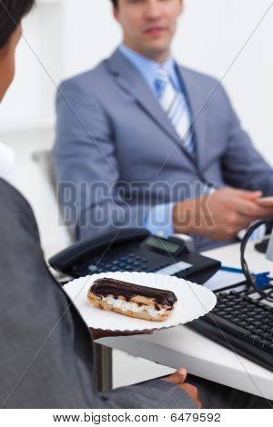 Close-up Of A Businesswoman Carrying A Pastry To Her Desk