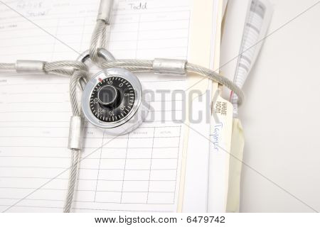 Stack Of File Folders Secured With Padlock