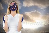 Excited australia fan in face paint cheering against large football stadium under cloudy blue sky poster