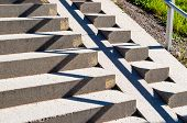 Shadow and light makes zigzag pattern on stone stairs. Small patch of green grass in corner. poster
