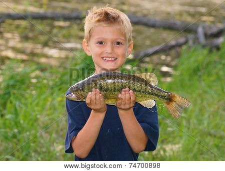 Boy with a big fish he caught next to a pond