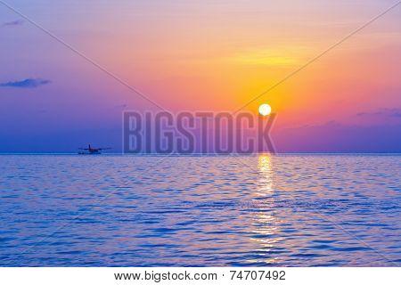 Seaplane at sunset - Maldives vacation background