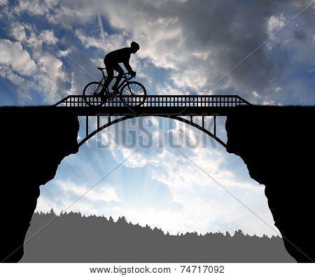 Cyclist riding across the bridge at sunset