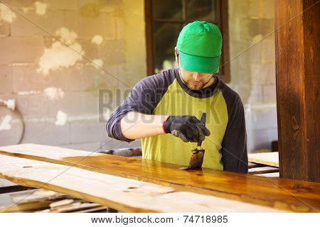 Handyman varnishing pine wooden planks in patio outside the new house poster
