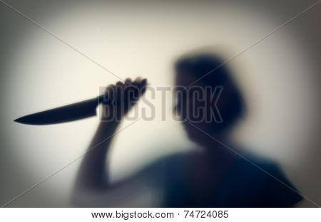 Shadowy figure of woman-killer with a knife behind glass