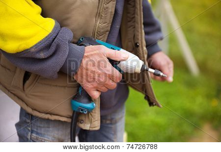 Detail of handyman holding electrical drilling machine poster