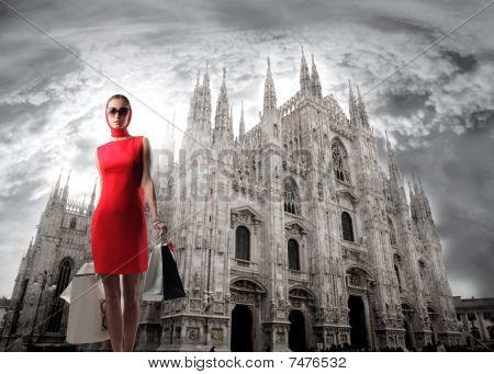 Portrait of a beautiful woman in red carrying some shopping bags standing in front of the Cathedral of Milan poster