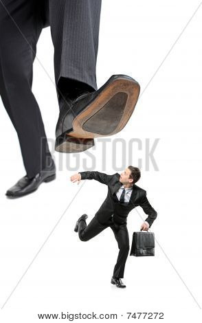 A businessman running away from a big foot