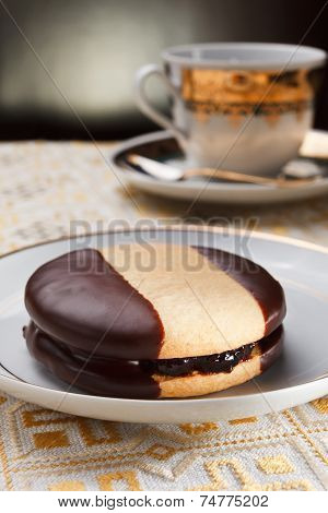 Homemade Delicious Pastry Filled With Jam, covered with dark chocolate and a cup of coffee poster