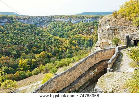 view of gorge mariam-dere and wall of chufut-kale town in Crimean mountains in autumn poster