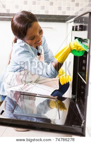 happy african woman cleaning oven in the kitchen