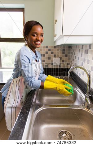 pretty african woman washing dishcloth at home