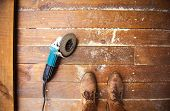 Electric grinder machine left on dusty wooden flooring with wood shavings poster