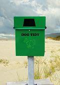 green disposal bin in a public place to keep beach clean poster