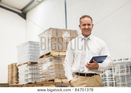 Manager standing with hand in the pocket holding tablet pc in a large warehouse