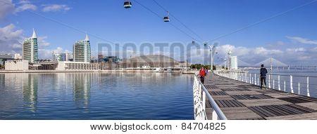 Lisbon, Portugal - February 01, 2015: People practicing sports on Passeio Ribeirinho. Atlantico Pavilion (MEO Arena). Vasco da Gama Tower and Bridge, Myriad Hotel and aerial tramway. Park of Nations