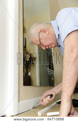 A senior man pulling nails from his baseboard as he upgrades his home.