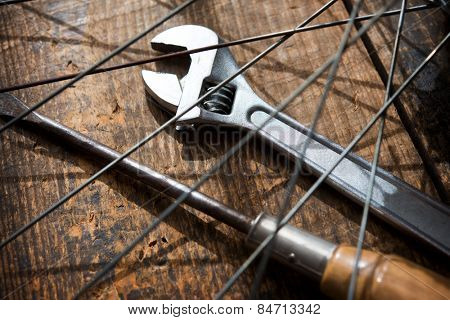 Bicycle repair. A monkey wrench and a screw driver beneath a bicycle wheel spokes. Focus is on wrench turn wheel knob.
