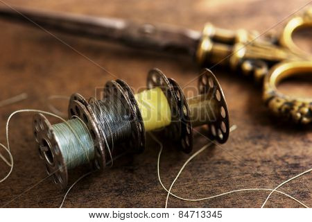 Vintage sewing machine bobbins with vintage gold ( brass ) scissors on a old grungy work table. Tailor's work table. textile or fine cloth making. Shallow depth of field.