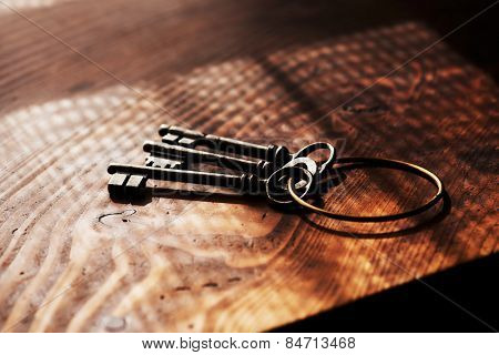 Vintage keys on an grungy old desk with window light shadow. Shallow depth of focus.