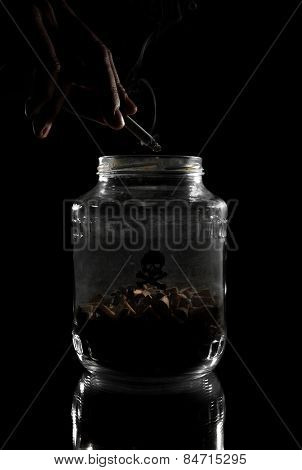 Smoker ashes cigarette into jar full of cigarette butts. Stop smoking concept. poster