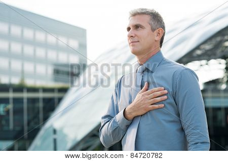 Portrait Of Mature Businessman Pledging With Hand On His Heart Outdoor poster