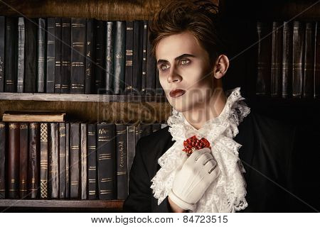 Handsome vampire nobleman studying ancient books in the library. Halloween. Dracula costume.