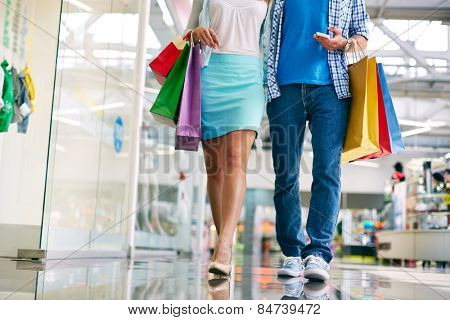 Legs of young couple of shoppers walking down mall