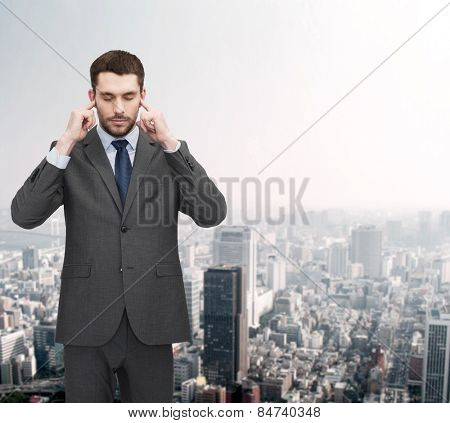 businss, office and education concept - annoyed businessman covering his ears with his hands