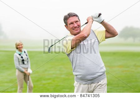 Happy golfer teeing off with partner behind him on a foggy day at the golf course