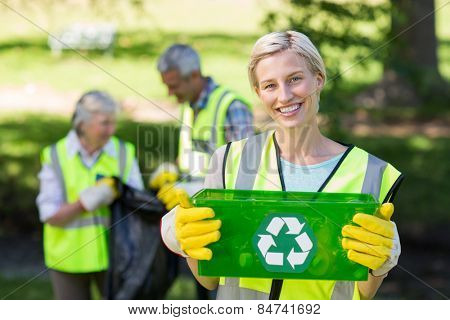 Happy mother holding recycling case on a sunny day