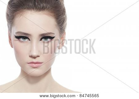 Hi-key portrait of young beautiful girl with stylish cat eye make-up over white background