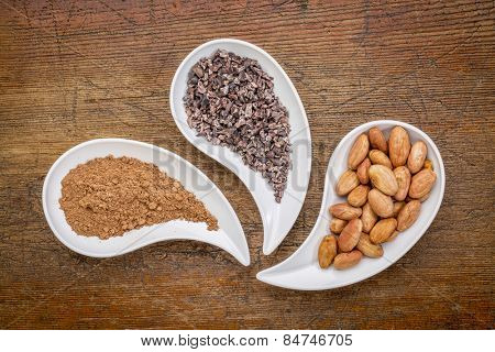 cacao beans, nibs and powder - top view of teardrop shaped bowls against rustic wood