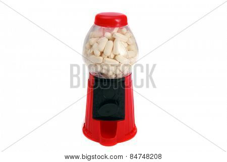A toy gum ball machine filled with white pills and drugs. Representing the dangerous access to illicit drugs. Illegal drugs are as easy to obtain as gum balls if you ask the right people. isolated