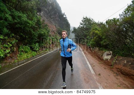 Male runner jogging and running on road in rain in jacket and long tights. Fit fitness model man working out living healthy lifestyle training for marathon. Young caucasian model in his 20s.