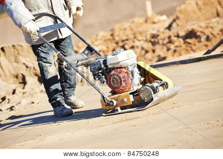 builder worker at sand ground compaction with vibration plate compactor machine before pavement roadwork poster