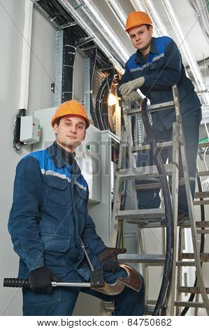 two electrician builder engineers workers installing industrial cable into fuse box