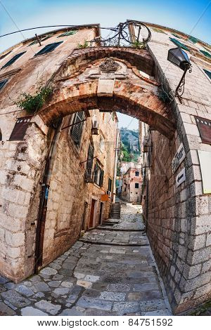 Fish-eye lens look of the old city on sky background. Kotor. Montenegro. Signs on the walls indicate the entrance to the old fortress