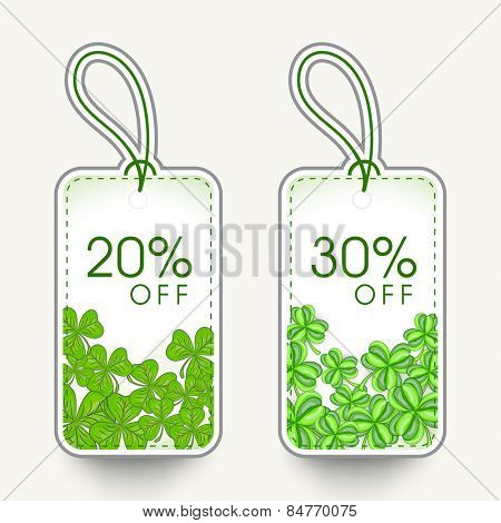 20% and 30% discount offer sale tags with green shamrock leaves for Happy St. Patrick's Day celebration.