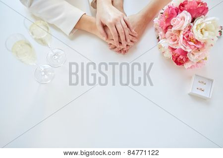 people, homosexuality, same-sex marriage and love concept - close up of happy lesbian couple hands with flower bunch, champagne glasses and wedding rings