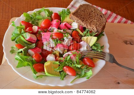 Mixed vegetable salad with crab sticks and avocado