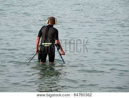 Man looking for underwater metal objects