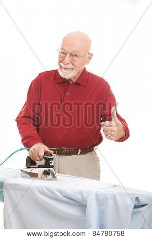Senior man doing his own ironing and giving a thumbs up sign.  Isolated on white.