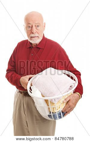 Confused senior man does laundry for the first time.  Isolated on white.