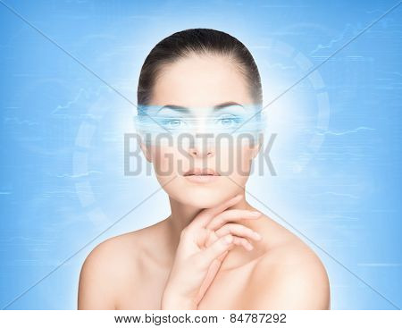 Young and attractive woman from future with the laser hologram on her eyes (eye scanning technology, optometry and virtual reality concept) poster