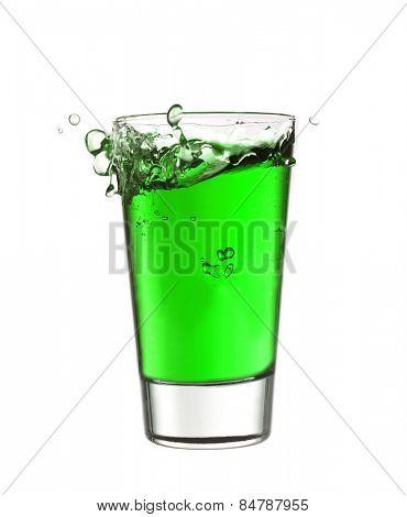 Splash in a glass of green lemonade isolated on white background